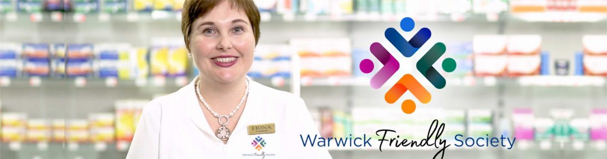 A smiling pharmacist with the logo.